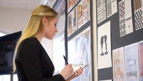 检查委员会和做笔记的年轻女性设计师 股票录像