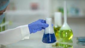 检查在烧瓶的实验员反应与散发烟的蓝色物质 影视素材