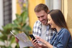 检查电话和地图的游人愉快的夫妇  免版税库存图片