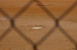 棒球场通过篱芭显示本垒板 库存图片