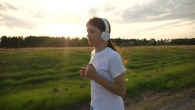 概念健康生活方式 少女向体育求助并且听到与耳机的音乐 跑步在路的女孩  股票录像