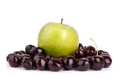 樱桃莓果和一个大绿色苹果在白色背景被隔绝的关闭宏指令 图库摄影