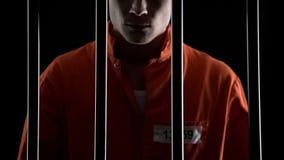 橙色制服的在监狱酒吧后,谋杀的服务的终身监禁罪犯 库存照片