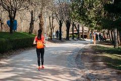 橙色T恤杉的女孩游人走与背包的在路的公园 免版税库存图片
