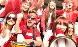 欢呼与旗子的年轻非职业橄榄球支持者爱好者观看地方足球杯子比赛在体育场-朋友人小组与 库存照片