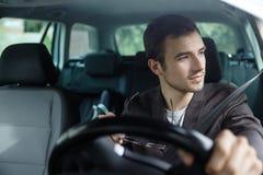 欢欣的年轻人看低谷窗口,当驾驶他的汽车时 他拿着他的玻璃在他的右手 他的左手 免版税图库摄影