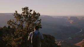 步行与背包的慢动作愉快的活跃年轻旅游人在史诗大峡谷附近夏天日落风景视图  股票视频