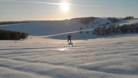 步行在多雪的山顶部的鸟瞰图年轻人在美好的冬天日落 有迁徙的杆的男性登山家 影视素材