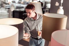 殷勤地控制灯质量的Tricenarian男性采购员在商店 免版税图库摄影