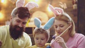 母亲、父亲和儿子绘鸡蛋 愉快的家庭为复活节做准备 逗人喜爱的小孩男孩佩带的兔宝宝 股票视频