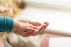 母亲使用她的手握她的婴孩的微小的手做感觉她的爱的他,温暖和安全 库存图片