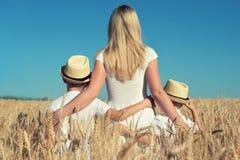 母亲和两个儿子互相拥抱和站立看麦子收获 免版税库存图片