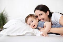 母亲和男婴在床上 免版税图库摄影