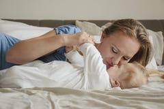 母亲特写镜头画象有她的婴孩的在床上在卧室 年轻有吸引力的妈妈爱她的儿子 愉快的系列 日母亲s 图库摄影