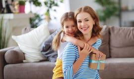 母亲节快乐!儿童女儿给母亲一花束郁金香和礼物 库存图片