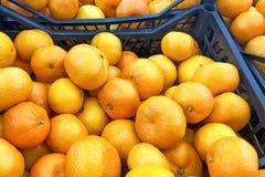 水多的橙色蜜桔桔子,普通话,柑桔,与叶子的柑橘水果在市场上 免版税库存照片