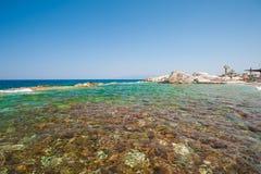 水的天蓝色的表面,在岸的清楚的水 免版税库存图片