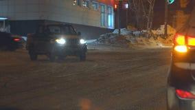 汽车在沿一条多雪的街道的晚上通过在城市 影视素材