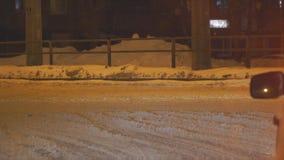 汽车在沿一条多雪的街道的晚上通过在城市 股票视频