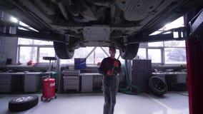 汽车服务、技工人在汽车下在推力在检查期间和修理在车间 股票录像