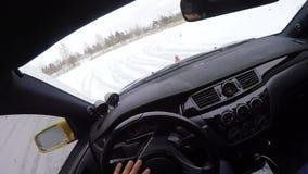 汽车由在积雪的湖的冰冷的轨道驾驶在冬天 在看法里面的客舱 赛跑在雪赛马跑道的跑车在冬天 股票录像