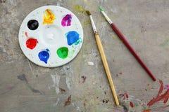 油漆刷和水彩油漆,在桌污迹的调色板颜色、教育和艺术对象,顶视图 库存照片