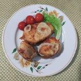 油煎的鱼三个片断与洋葱圈的在板材 免版税库存照片