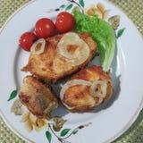 油煎的鱼三个片断与洋葱圈的在板材 免版税图库摄影