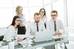 沟通的商人工作和,当坐在办公桌时 免版税图库摄影