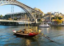 波尔图/葡萄牙- 2010年11月27日:城市、金属Dom雷斯桥梁在杜罗河河和游人Rabelo小船的全景 免版税库存照片