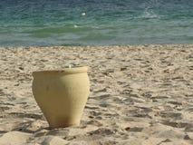 泥罐在沙子站立在海,非洲旁边 免版税库存照片