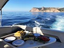 海岸的餐馆反对爱琴海海岸大海和游艇口岸在切什梅的 与牛肉板材的大理石表  免版税库存图片