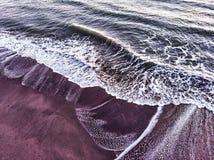海浪断裂到与回流的海岸里 免版税库存照片