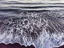 海浪断裂到与回流的海岸里 免版税库存图片