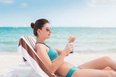 海滩睡椅的一名可爱的年轻深色的妇女喝在一个海滩的冰镇啤酒在墨西哥 免版税库存照片