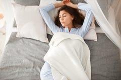 浅兰的睡衣的俏丽的深色的女孩在床上睡觉在灰色板料的米黄毯子下 免版税库存图片