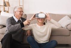 测试与丈夫的愉快的成熟妇女VR玻璃 免版税库存照片