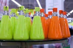 液体皂、卫生间陶瓷辅助部件以绿色和橘黄色的浴皂盒分配器在玻璃搁置在商店关闭  免版税库存图片