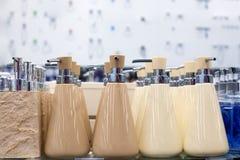 液体皂、卫生间陶瓷辅助部件在灰棕色和白色的浴皂盒分配器在玻璃搁置在商店关闭  免版税图库摄影