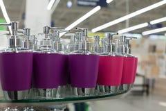 液体皂的浴皂盒pastic分配器的卫生间和在紫色和粉色的金属辅助部件在玻璃搁置在商店clos 库存图片