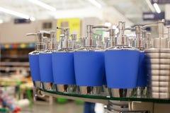 液体皂的浴皂盒pastic分配器的卫生间和在蓝色的金属辅助部件在玻璃在商店搁置紧密,洗手间 库存图片