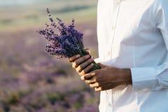 淡紫色花束在一个人的手上 库存照片