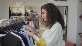 深色的夫人在商店大厅里观看在机架的衣裳 影视素材