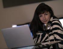 深色的女孩在家坐在膝上型计算机后,微笑着并且看与一杯的照相机酒 免版税图库摄影