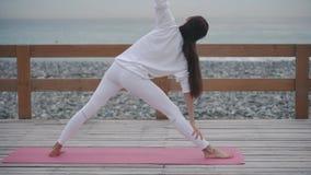 深色的妇女在海滨做着瑜伽asanas户外自白天 股票视频