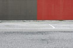 混凝土墙绘了半红色和半灰色与一条柏油路在前面 拷贝空间的背景 免版税图库摄影
