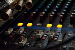混音器在黑暗的轻的背景的控制板在音频控制室 库存图片