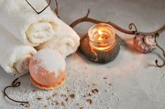 温泉放松概念 白色特里毛巾、石头、一个蜡烛和一颗炸弹海盐浴的在灰色织地不很细背景 免版税库存照片