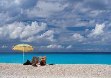 游人在沙滩伞和美丽的海滩Myrtos下用清楚的绿松石水在一好日子在的爱奥尼亚海 库存照片