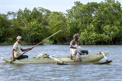渔夫用浆划他们的横跨Pottuvil盐水湖的舷外浮舟 免版税图库摄影